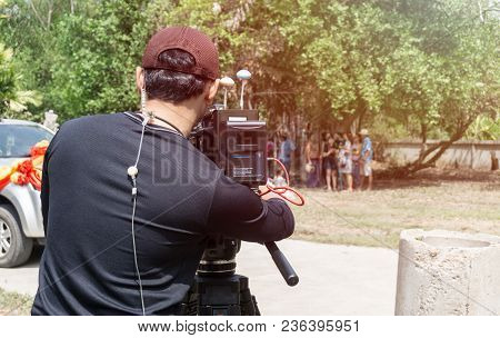 Camera Working On The Street., Back Of Asian Cameraman Using A Professional Camcorder Outdoor Filmin