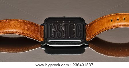 Smart Watch With A Brown Leather Strap On A Reflective Background