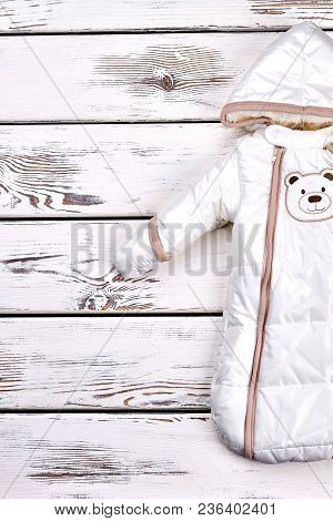 Infant Kids Warm Winter Romper. Childs Hooded Outerwear, Old Wooden Background, Top View. Kids Warm
