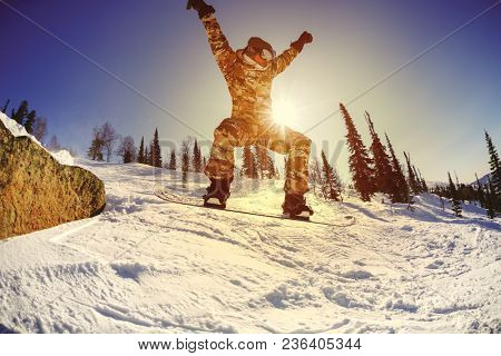 The snowboarder jumps from the springboard against the blue sky in the backlight. Sheregesh resort. Russia.
