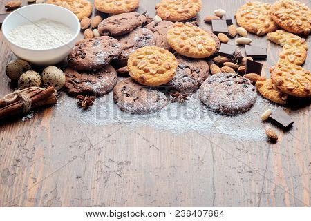 Chocolate Chips Cookies, Peanut Cookies And Scattered Nuts On Dark Rustic Texture With Copy Space Fo