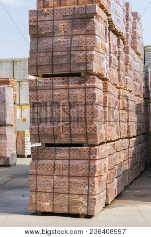 Several Pallets With Concrete Brick Stacked On Top Of Each Other In Depot. New Bricks On Pallets.