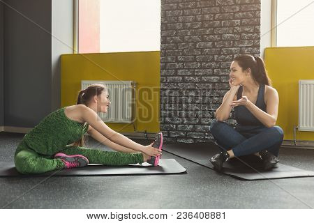 Two Happy Women Exercising At Fitness Club. Female Friends Training And Gossiping At Gym, One Stretc