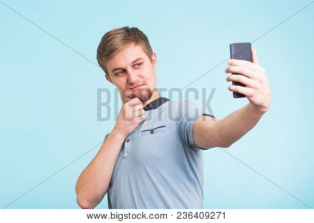 Funny Man Grimacing While Making Selfie On Blue Background