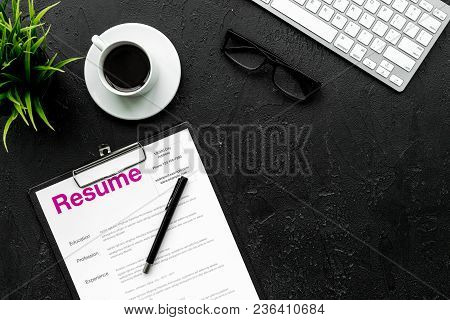 Review Resumes Of Applicants. Resume On Black Work Desk With Coffee, Glasses, Keyboard Top View.