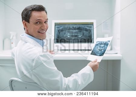 Feeling Happy. Exuberant Experienced Dentist Holding An Image And Working On Her Advanced Device