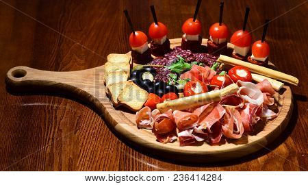 Board With Snacks On Wooden Table. Snacks Appetizing Served On Round Board. Restaurant Dish Concept.