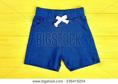 Baby Boy Casual Shorts. Toddler Boy Brand Textile Short Pants On Yellow Wooden Background. Dark Blue