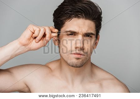 Close up beauty portrait of half naked concentrated young man using tweezers isolated over gray background