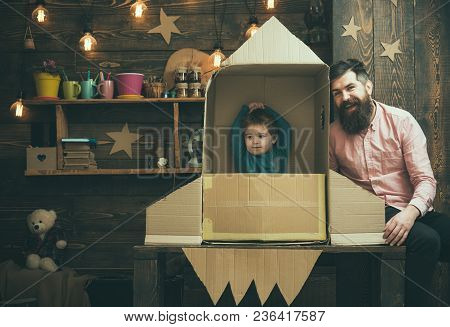 Rocket Launch Concept. Kid Happy Sit In Cardboard Hand Made Rocket. Boy Play With Dad, Father, Littl
