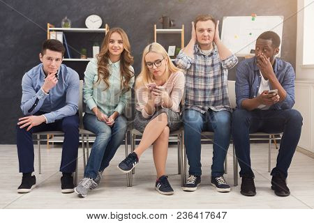 Group Of Business People Sitting On Chairs And Working. Successful Team Using Gadgets And Grimacing,