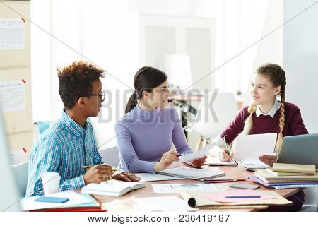 Two girls and guy sitting in library after lessons and preparing for essay - reading and discussing sources of information