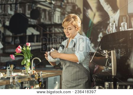 Smiling Barista Wiping Cups At Cafe Counter. Portrait Of Middle-aged Woman In Uniform At Her Working