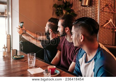 Group Of Arab Friends Taking Selfie In Lounge Bar. Mixed Race Young Men Having Fun In Restaurant. Be