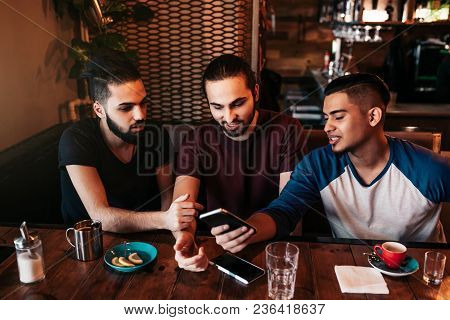 Group Of Mixed Race Young Men Using Phone And Talking In Lounge Bar. Multiracial Friends Having Fun