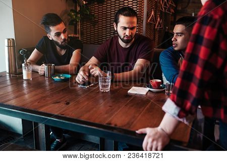 Arabian Friends Discuss Their Order With Waitress In Restaurant. Choosing Food To Order. Cafe And Re