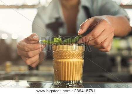 Closeup Of Female Hands Preparing And Serving Tasty Cold Coffee Non-alcoholic Cocktail With Mint. Ba
