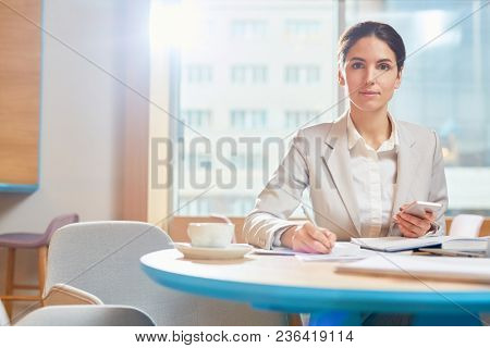 Young serious businesswoman looking at camera while sitting by table in cafe and making working notes