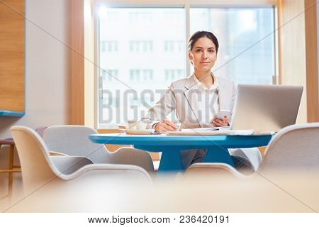 Confident young manager looking at camera while sitting in cafe and planning work