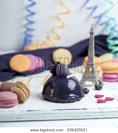 Lilac Round Cake With Macarons On A White Wooden Board, Behind A Multicolored Paper Serpentine