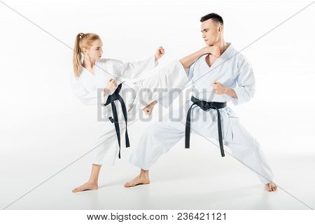 Female Karate Fighter Kicking Male Partner Isolated On White