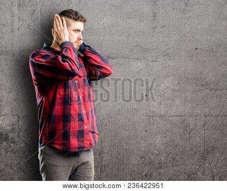 Young handsome man covering ears ignoring annoying loud noise, plugs ears to avoid hearing sound. Noisy music is a problem.