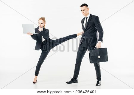Businesswoman Holding Laptop And Kicking Businessman Isolated On White