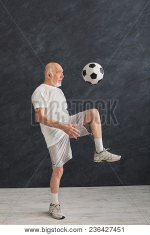 Cheerful Senior Man Kicking Soccer Ball Indoors, Black Background. Hobby And Active Lifestyle In Any