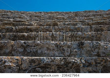 Closeup photo of steps of Roman amphitheatre in the ruins of Hierapolis, in Pamukkale, near modern turkey city Denizli, Turkey.