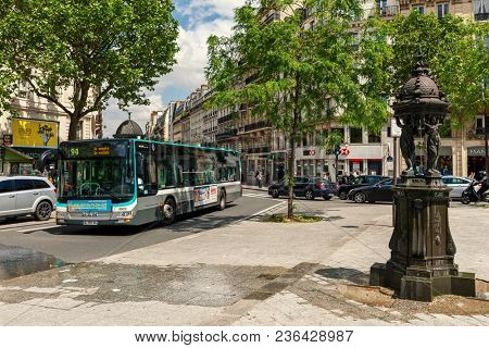 PARIS, FRANCE - MAY 25, 2016: Wallace fountain, public bus and cars on the street of Paris - capital and largest city of France it is also one of the popular travel destinations.