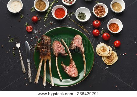 Grilled Rack Of Lamb. Bbq Meat With Spices Assortment On Green Plate On Black Table, Restaurant Food