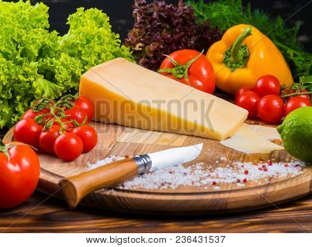 Wooden Board With Parmesan Cheese, Fresh Cherry Tomatoes, Lettuce, Sea Salt And Red Pepper. The Knif