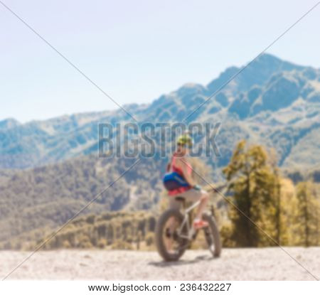 Blurred photo of woman in helmet riding bike