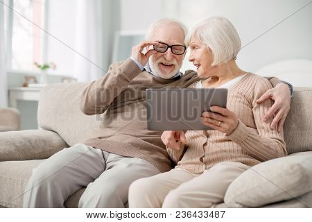 Pleasant Rest. Delighted Aged Man Fixing His Glasses While Looking At The Tablet Screen