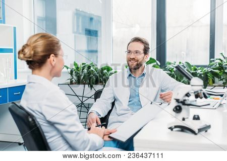 Scientists In Lab Coats And Eyeglasses Discussing Work At Workplace In Lab