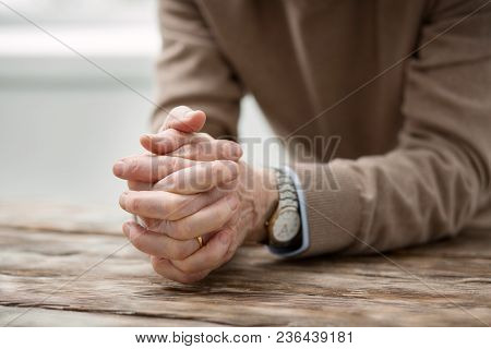 Feeling Of Loneliness. Unhappy Cheerless Aged Man Holding His Hands Together While Feeling Lonely