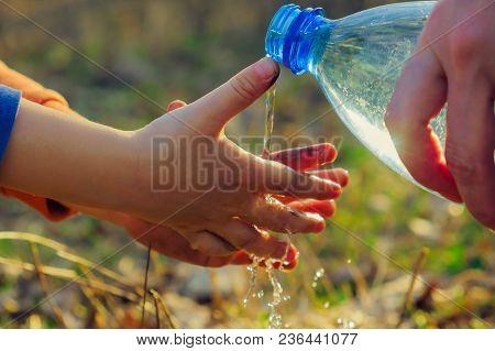A Small Boy Child Washes His Hands On A Picnic With His Mother. Outdoor Hygiene Before Eating