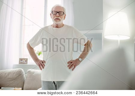 At Home. Pleasant Elderly Man Standing In The Room While Closing His Eyes