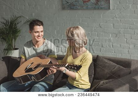 Smiling Boyfriend Giving Acoustic Guitar To Girlfriend At Home