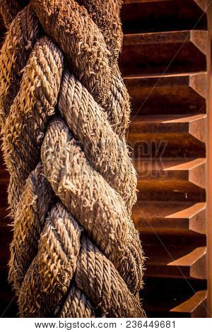 Thick Braided Rope From A Boat, Tied To A Cogwheel