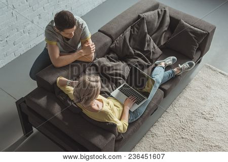 High Angle View Of Girlfriend Using Laptop And Boyfriend Leaning On Sofa At Home