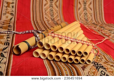 Panpipes and flute from South America on a textile background