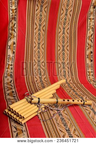 Panpipes and flute from South America on a textile background with space for text