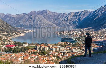 Tourist With A Hat Admiring The Stunning Landscape Of The Bay Of Kotor In Montenegro As Seen From Th