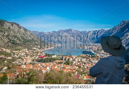 Female Tourist With A Hat Admiring The Stunning Landscape Of The Bay Of Kotor In Montenegro As Seen