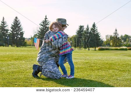 Soldier Reunited With His Daughter. Child With Usa Flag Is Hugging Her Military Daddy Outdoor In The