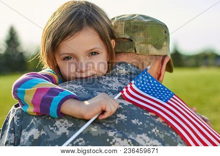 Little Girl With Us Flag Is Hugging Her Father. Happy Reuinion Of Us Family.