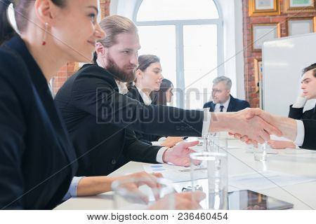 Business people shaking hands at meeting in office after discussion of financial charts