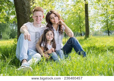 Happy family with man, woman and child leaning on tree in city park