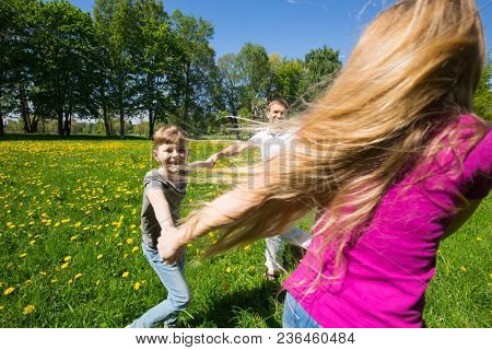 Happy family with children having fun round dancing holding hands together in city park